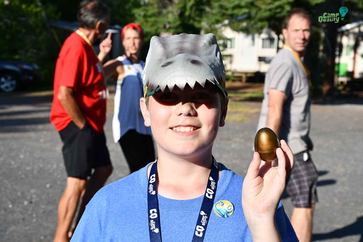 Camper Gryphon showing off his Golden Egg – his ticket to the front of the lunch line tomorrow! He's also sporting a really cool dinosaur cap.