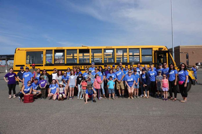 Camp Quality NWO campers and Companions gather in front of the bus for a group photo.