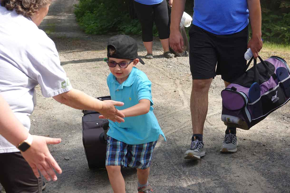 Camper Hunter receiving high fives as he hauls a suitcase double his size…he politely declined all offers of help.