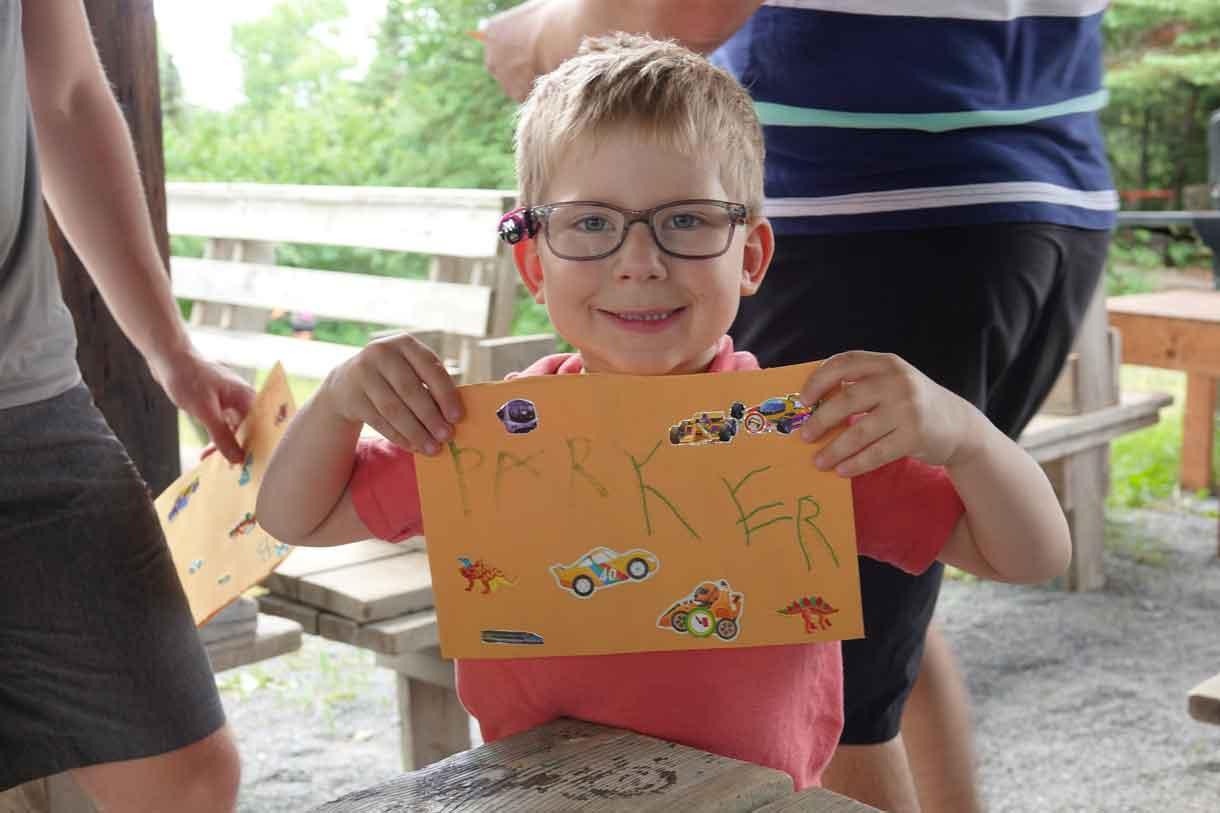 Camper Parker holding up his freshly decorated Q-Mail envelope.