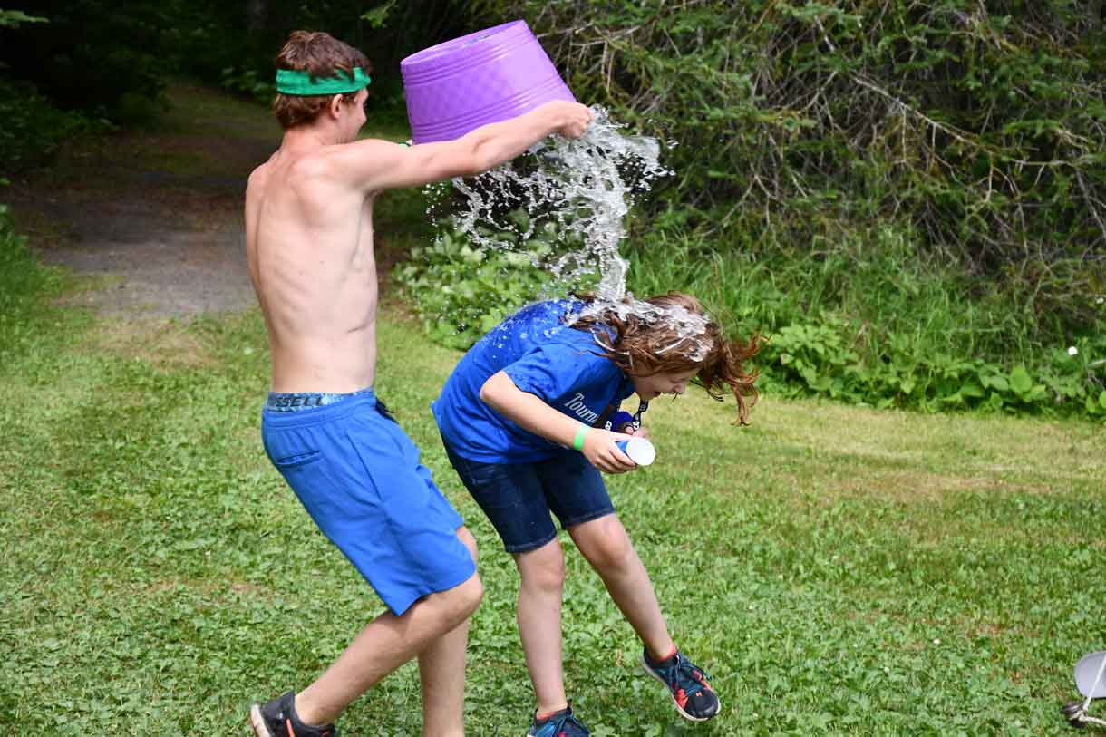 Camper Zeke dousing his sister Nevaya with the water that was SUPPOSED to be for the Survivor Challenge!