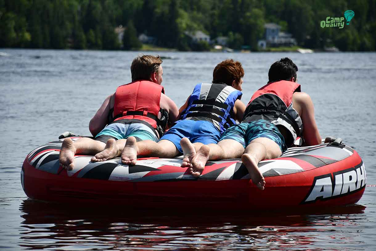 (from left) – Volunteer Braeden, camper Zeke and volunteer Brady taking a spin on the tube!