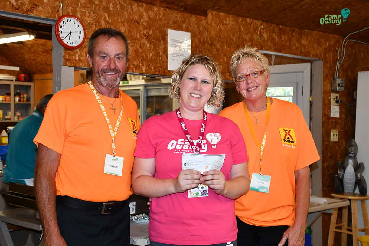 Mike (left) and Kristy (right) from KOA present Camp Director Ashleigh with a cheque $4000.