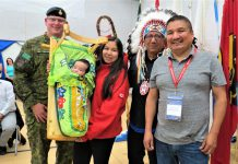 New Canadian Ranger Shawnda Mamakwa holds her son, Ashton, two months, in a traditional Oji-Cree cradleboard. She is flanked, from left, by Lieutenant-Colonel Matthew Richardson, Grand Chief Alvin Fiddler, and Kingfisher Lake Chief Eddie Mamakwa. - Image Sgt Peter Moon
