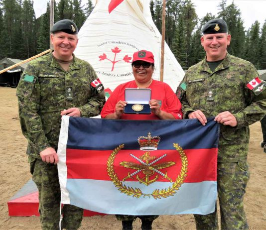 Brigadier-General Conrad Mialkowski, lzeft, commander of 4th Canadian Division, left, presents a Canadian Armed Forces Unit Commendation to 3rd Canadian Ranger Patrol Group for saving lives in Northern Ontario. The award consists of a pennant, a scroll, and a gold medallion. Master Corporal Harriet Cutfeet, centre, holds the medallion and Lieutenant-Colonel Matthew Richards, right, holds the pennant.