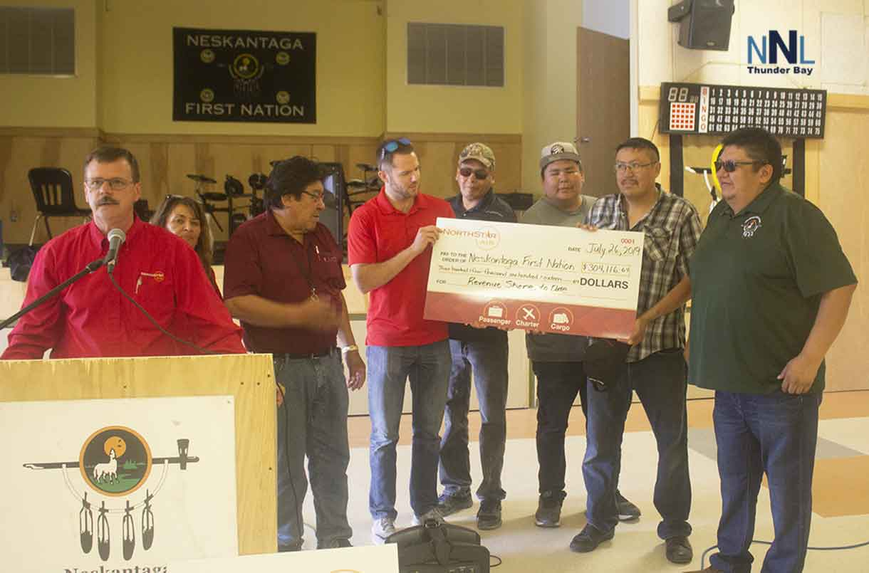North Star Air Vice President  Tom Meilleur and Neskantaga First Nation Chief Chris Moonias and members of his Council accept revenue sharing cheque