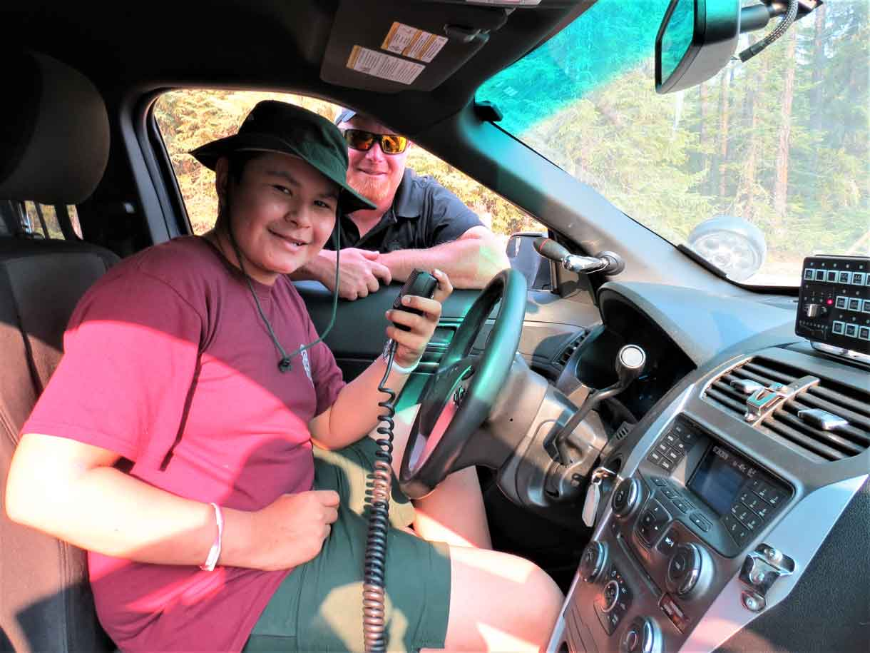 Constable Gary Camberly shows Junior Canadian Ranger Tanner Wesley of Constance Lake how the radio works in a Thunder Bay Police cruiser.  credit Sergeant Peter Moon, Canadian Rangers