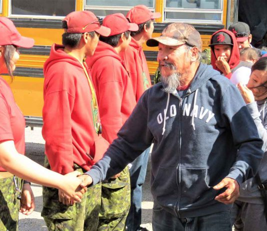 An elder thanks a Canadian Ranger as he walks from a bus to a waiting evacuation plane.