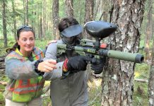 Constable Roxanne LeGrande guides Junior Canadian Ranger Wilbert Shisheesh on how to shoot on the paintball site. - Photo Sgt Peter Moon Canadian Rangers