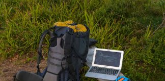Portable technology, solar panel, tablet, laptop and backpack in a forest