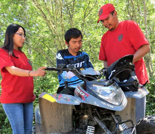 Junior Canadian Ranger Jeremiah Cutfeet, centre, receives safety instructions from Corporal Angela Tait, left, and Master Corporal Orion McKay, right, before going on an off road trail ride.