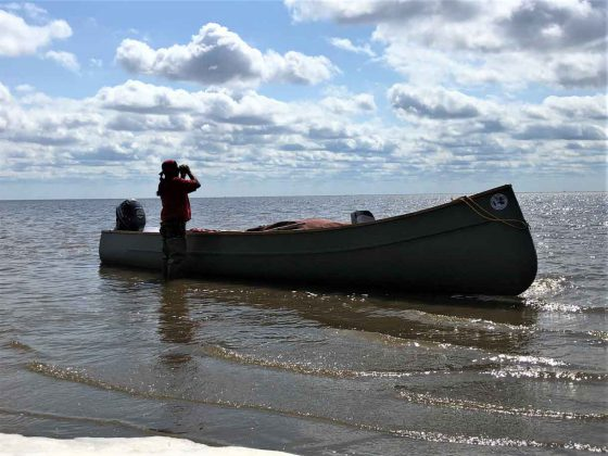 Sergeant Thomas Scott of Fort Albany First Nation uses binoculars to see how far the tide has gone out on James Bay.