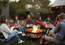 Teenage friends sit round a fire pit
