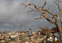 A man walks among debris at the Mudd neighborhood, devastated after Hurricane Dorian hit the Abaco Islands in Marsh Harbour, Bahamas, September 6, 2019. REUTERS/Marco Bello