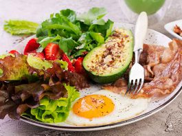 Plate with a Fried egg, bacon, avocado, arugula and strawberries.
