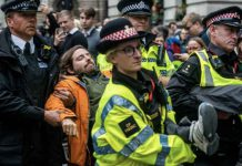 Police officers remove a volunteer with the Extinction Rebellion who was protesting the role of banks in financing fossil fuel projects undermining the 2015 Paris Agreement to curb climate change, in London, Britain, October 14, 2019, in this image obtained via social media. Louise Jasper via REUTERS