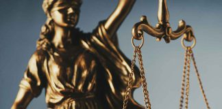 Figure of Justitia or Justice holding the scales of justice with close up focus to the scales symbolic of the law over grey