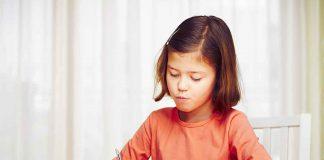 Little girl is doing her homework for elementary school.