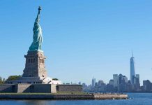 Statue of Liberty island and New York city skyline in a sunny day, blue sky