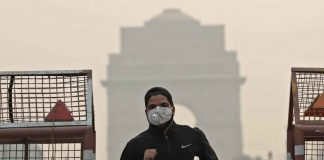 A man wearing a mask runs past the India Gate on a smoggy morning in New Delhi, India, October 28, 2019 REUTERS/Adnan Abidi