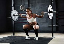 Active young woman lifting weights