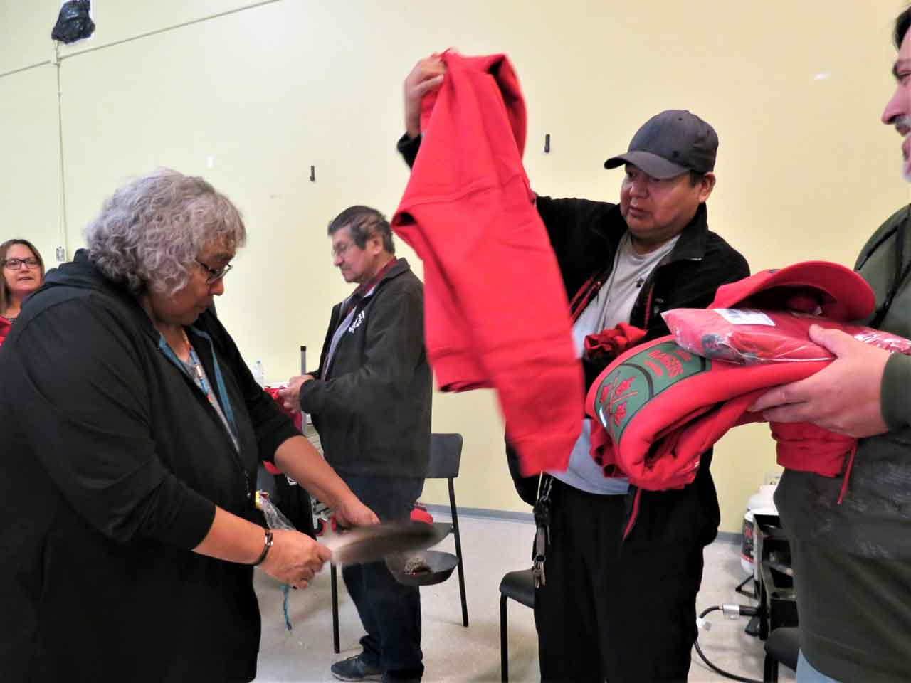 Aroland Elder Nora Atlookan smudges the uniform items issued to newly sworn-in Canadian Rangers