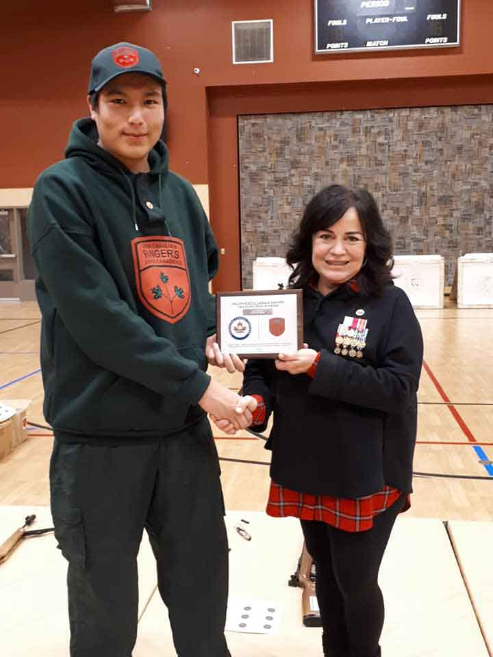 Junior Canadian Ranger Ian Kakekaspan receives a plaque and cheque from Kerry Vance, a director of Canada Company. Photo Credit - Corporal Lori Kendall, Canadian Rangers