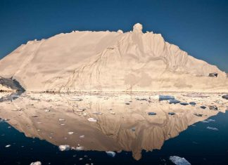 The midnight sun casts a golden glow on an iceberg and its reflection in Disko Bay, Greenland. Much of Greenland's annual mass loss occurs through calving of icebergs such as this. - CREDIT Ian Joughin, University of Washington