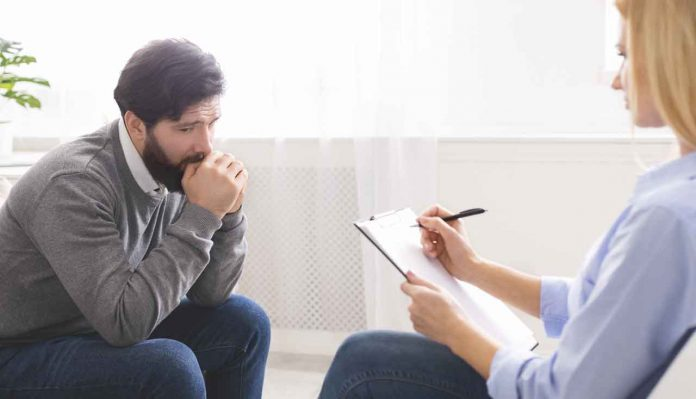 Depressed man getting psychological treatment at office.