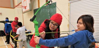 Ranger Nadine Strang of Pikangikum First Nation helps a girl using a bow and arrow for the first time in North Spirit Lake First Nation