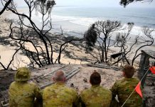 Soldiers sit on a beach amongst burnt trees where people had previously taken shelter during a fire on New Year's Eve in Mallacoota, Australia January 10, 2020. REUTERS/Tracey Nearmy
