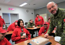 Warrant Officer Sheldon DeWolfe, an army instructor, prepares to cut a celebratory cake with a ruler for the Canadian Ranger students.