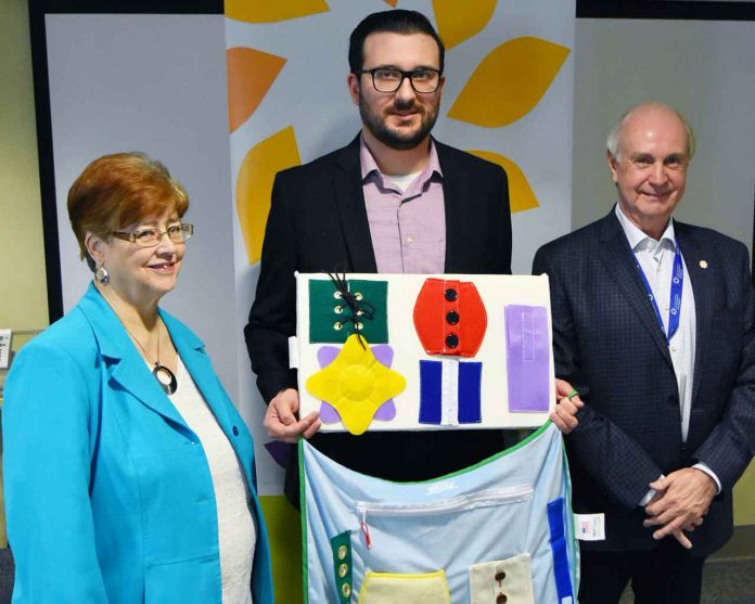 Matthew Shonosky (centre), Manager of the HELP program, showing samples of the Alzheimer's/Dementia activity items funded by a Family CARE grant, alongside Shirley Wragg (L), Vice President of the Volunteer Association and Barry Streib (R), Secretary and Chair, Governance for the Thunder Bay Regional Health Sciences Foundation