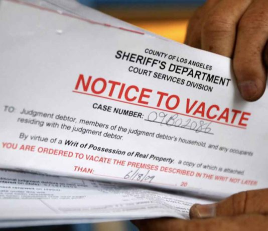 ARCHIVE PHOTO: A man holds up his eviction notice in Los Angeles, June 11, 2009. REUTERS/Lucy Nicholson