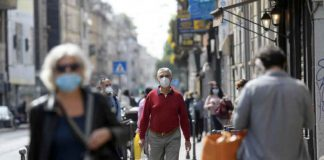 People wearing protective masks walk in an increasingly busy street, amid the coronavirus disease (COVID-19) outbreak, in Milan, Italy April 18, 2020. REUTERS/Daniele Mascolo