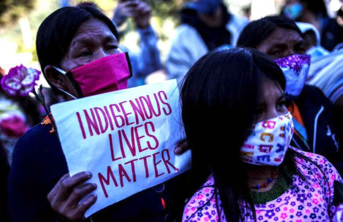 FILE PHOTO: Demonstrators wearing face masks protest in front of a military battalion, against the reported rape of an Embera Chami indigenous girl by soldiers, in Bogota, Colombia June 29, 2020. REUTERS/Luisa Gonzalez/File Photo
