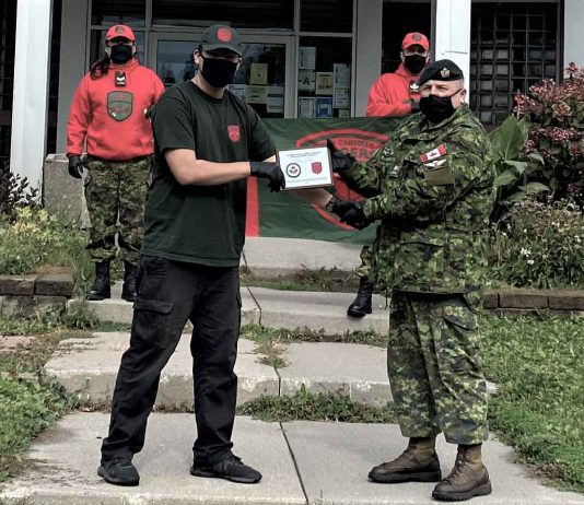 Junior Canadian Ranger Michael Baxter, left, receives a cheque for $1,000 to further his education and a plaque from 2nd Lieutenant Jack Teskey of the Canadian Army. Photo credit: Corporal David M. Thompson