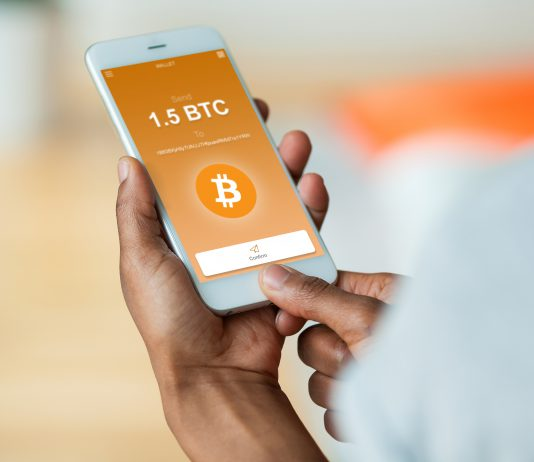African american person sending a bitcoin btc crypto transaction using mobile phone wallet - Black people