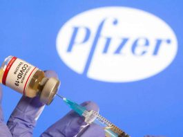 "A woman holds a small bottle labeled with a ""Coronavirus COVID-19 Vaccine"" sticker and a medical syringe in front of displayed Pfizer logo in this illustration taken, October 30, 2020. REUTERS/Dado Ruvic/File Photo"