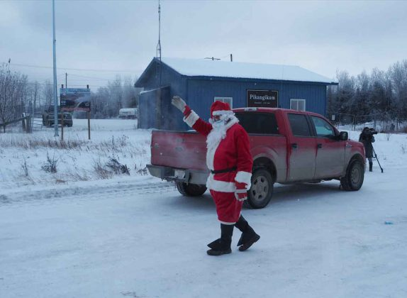 Santa waves at the people from the safety of the tarmac at the Pikangikum Airport