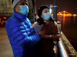 Fang Yushun warms the hands of his wife, Duan Ling, 36, during a cold winter's night as they take a walk outside, almost a year after the global outbreak of the coronavirus disease (COVID-19) in Wuhan, Hubei province, China December 16, 2020. REUTERS/Aly Song
