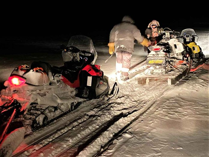 Master Corporal Mike Koostachin and Corporal Maurice Mack load a stranded Peawanuck snowmobiler's broken-down machine onto a toboggan after going to his aid. credit Master Corporal Jason Hunter, Canadian Rangers