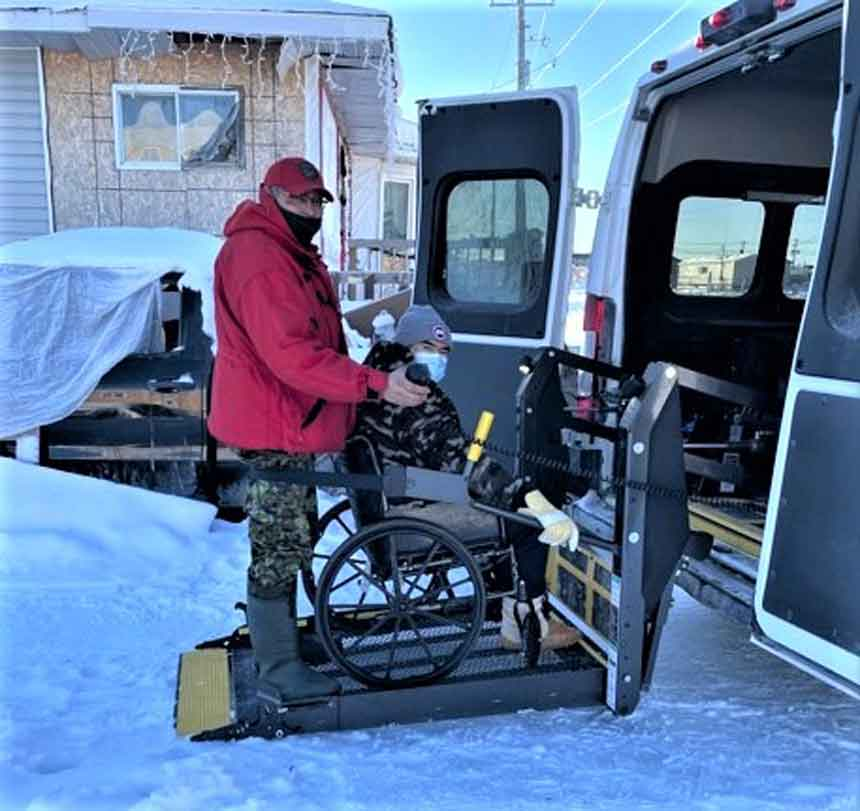 Corporal Dennis Sutherland helps an elder in Kashechewan into a wheelchair accessible vehicle to take her to the vaccination site. credit Sergeant John Sutherrland, Canadian Rangers