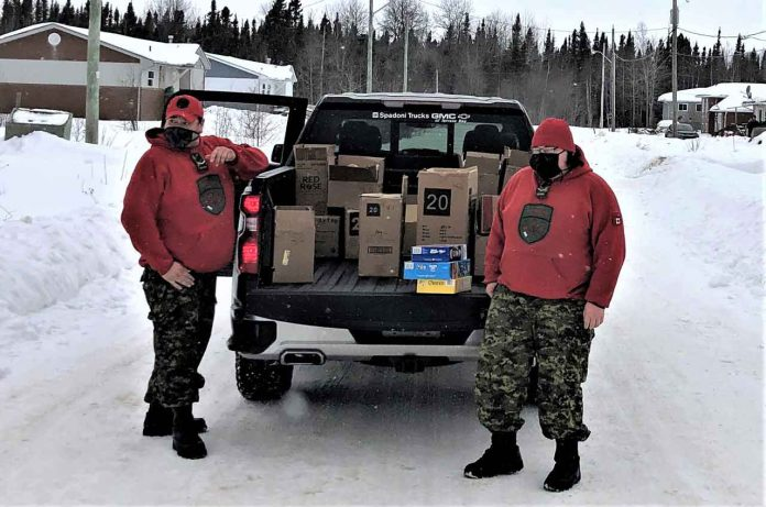 Rangers Jody Grenier and Curtis Waboose deliver food to homes in Ginoogaming in bitter cold temperatures. credit Warrant Officer Carl Wolfe