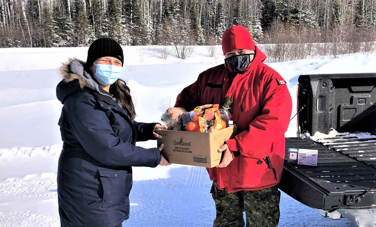 Community member Tracy Dore receives a box of Covid emergency supplies from Ranger Jody Grenier. credit Warrant Officer Carl Wolfe