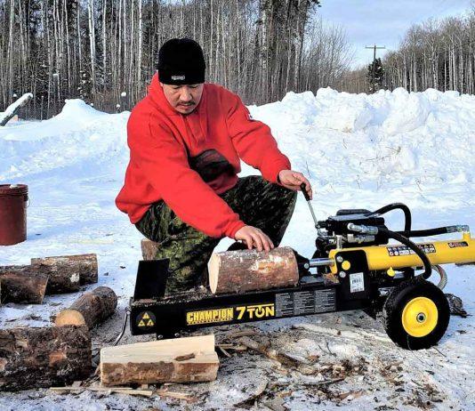 Master Corporal Shaun Kakegamic uses a wood splitter to prepare firewood for elders in Muskrat Dam. credit Sergeant Emily Beardy, Canadian Rangers