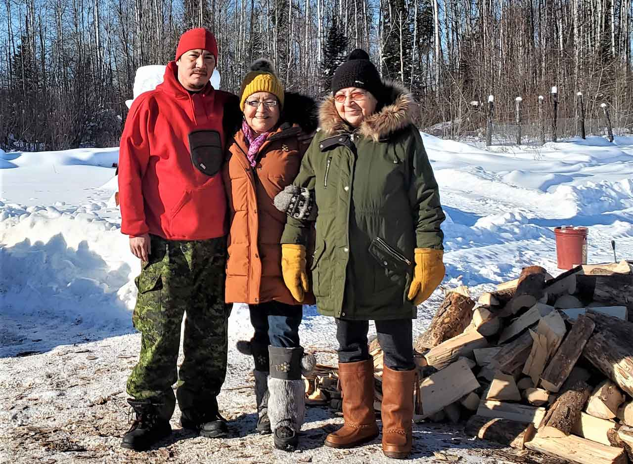 Master Corporal Shaun Kekegamc takes a break from cutting wood to talk with Elders Irene Ross and Flora Beardy.