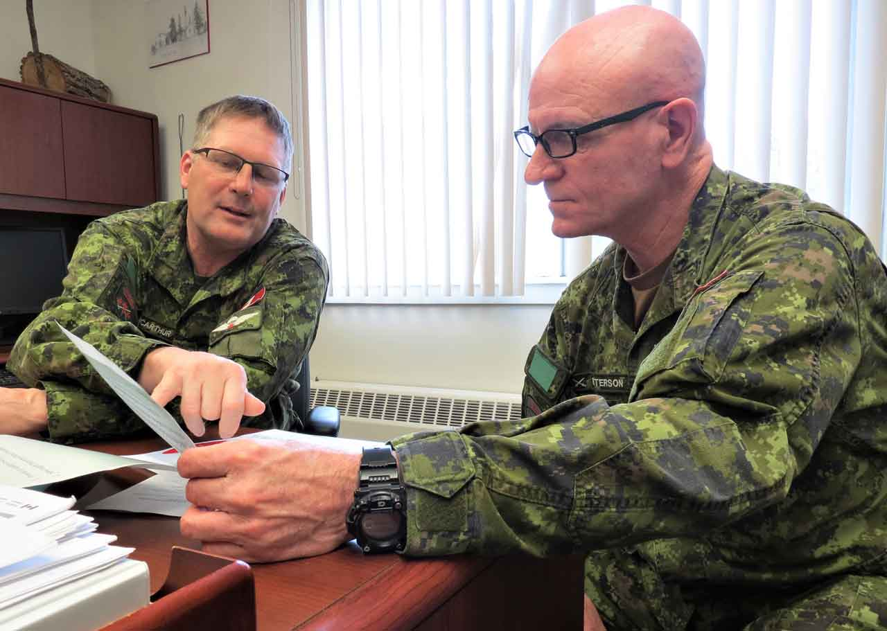 Lieutenant-Colonel Shane McArthur, who commands the Canadian Rangers of Northern Ontario, left, discusses a problem with Chief Warrant Officer Robert Patterson.