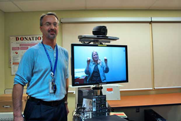 Bruce Bogacki (left) and Glenda Messier demonstrate the new wireless – and secure – videoconferencing equipment that will be used for American Sign Language interpretive services in the ICU and the Emergency Department