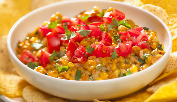 A summer favourite, corn blends with sweet smoked paprika for a tasty dip. Smoked paprika is the secret spice of Spain and is available in bulk stores and spice aisles. Serve with corn tortilla chips for dipping. Preparation Info: Preparation Time: 20 minutes Cooking Time: 10 minutes Makes: about 3 cup (750 mL), enough for 12 servings Ingredients: 4 large cobs Ontario Corn 2 tbsp (25 mL) butter 2 Ontario Green Onions, minced 4 cloves Ontario Garlic, crushed 2/3 cup (150 mL) reduced-fat mayonnaise 1/3 cup (75 mL) water 1/4 cup (50 mL) freshly grated Parmesan cheese 2 tsp (10 mL) smoked paprika 2 tsp (10 mL) fresh lime juice 1/2 tsp (2 mL) pepper 1/4 tsp (1 mL) salt Hot pepper or chipotle pepper sauce (optional) 1/4 cup (50 mL) finely diced seeded Ontario Tomatoes 2 tbsp (25 mL) minced fresh Ontario Coriander Preparation Instructions: Slice kernels from corn cobs to make 4 cups (1 L). In large skillet, melt butter over medium-high; cook corn, undisturbed, for 3 minutes or until starting to brown. Stir and cook for 2 minutes or until deep golden brown. Stir in green onions and garlic; cook for 1 to 2 minutes. Reduce heat to medium-low; stir in mayonnaise, water, cheese, paprika, lime juice, pepper and salt until smooth. Cook, stirring, until slightly thickened, 2 to 3 minutes. Season with hot sauce (if using). Spoon into shallow serving dish, such as pie plate; garnish with tomato and coriander. Serve warm or at room temperature. Nutritional Information: 1 Serving (2 tbsp/25 mL) Carbohydrates: 11.0 grams Calories: 114 Fat: 7.0 grams Fibre: 2.0 grams Protein: 3.0 grams Sodium: 220 mg